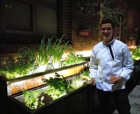 El chef Nelson Granados, junto a la huerta orgánica cultivada en el hotel.